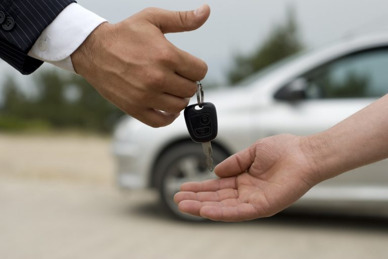 man handing car keys to someone else