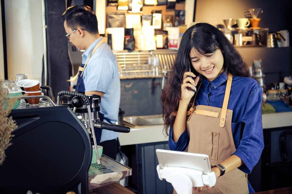 Barista talking order by phone in her shop