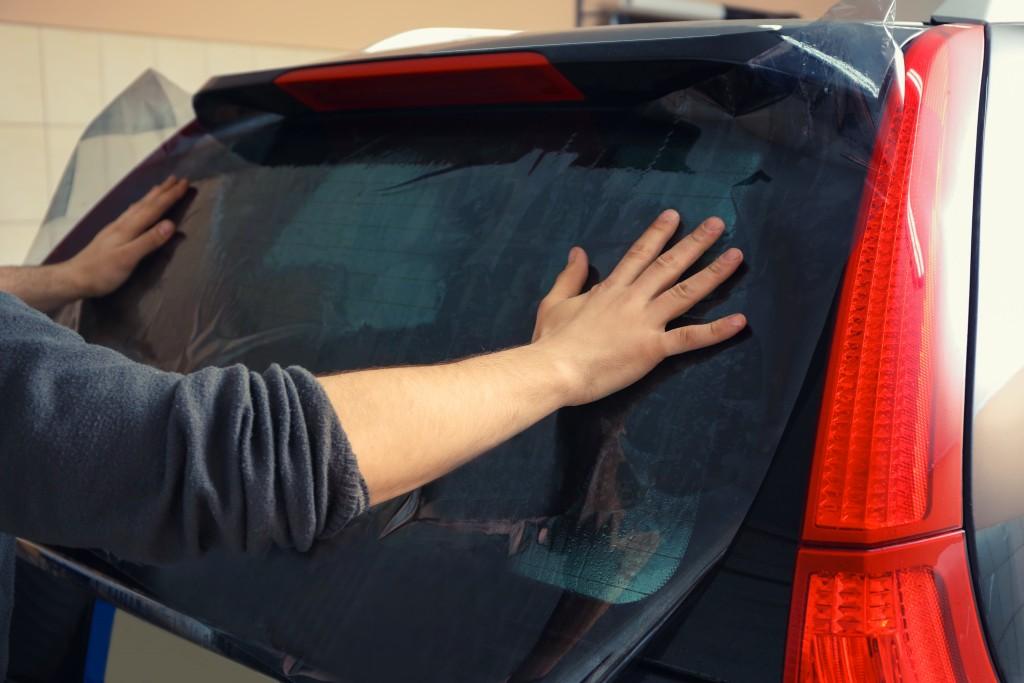 man tinting his car windows